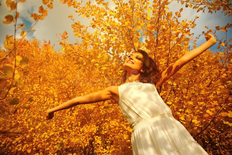A jovem mulher arma-se aumentado apreciando o ar fresco na floresta do outono fotos de stock