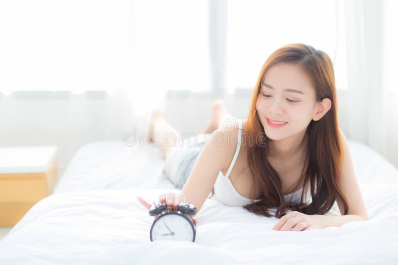 A jovem mulher asiática bonita desliga o despertador na manhã, acorda para o sono com despertador fotografia de stock royalty free