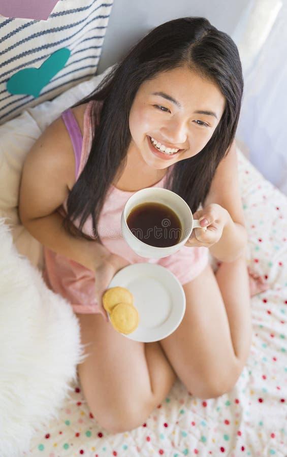 Jovem mulher asiática bonita que come o café da manhã na cama imagens de stock