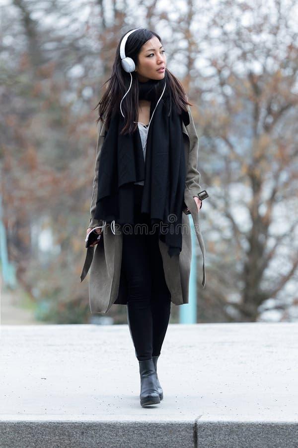 Jovem mulher asiática bonita que escuta a música com fones de ouvido ao andar na rua fotos de stock royalty free