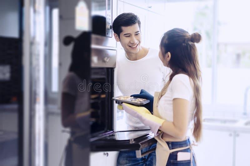 Jovem mulher asiática bonita que faz a cookie caseiro na cozinha em casa imagens de stock royalty free