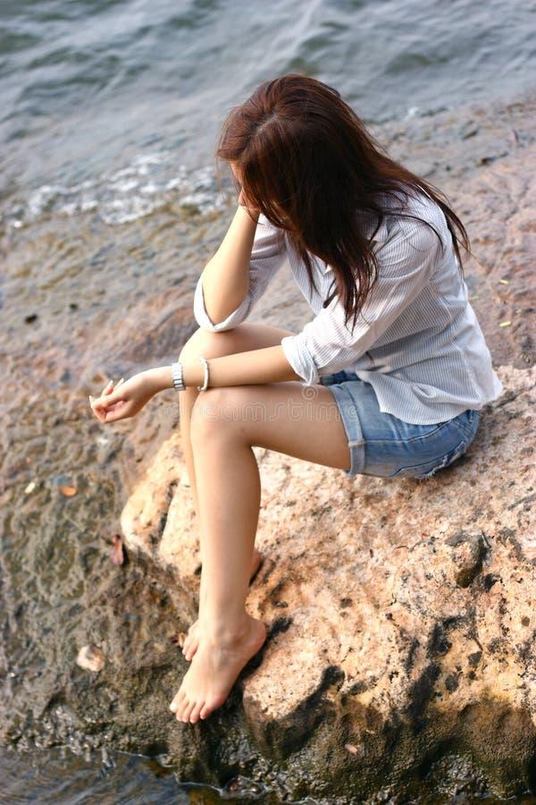 Jovem mulher asiática bonita que senta-se na rocha perto da praia fotografia de stock royalty free