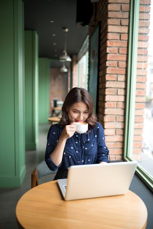 A jovem mulher asiática bonito bonita no café, aprecia beber o cof imagens de stock