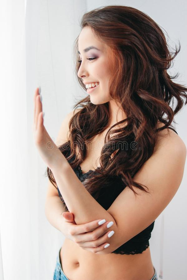 Jovem mulher asiática de sorriso sensual feliz da menina com cabelo encaracolado longo escuro no roupa interior preto que olha a  fotografia de stock