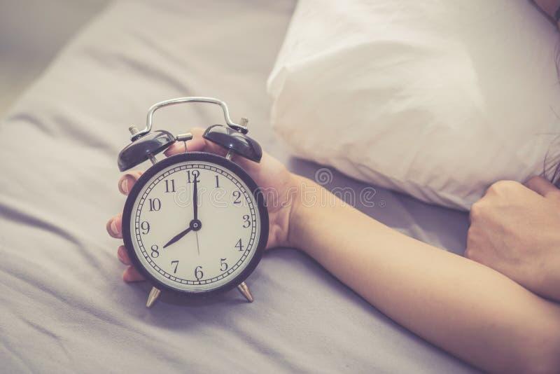 A jovem mulher asiática do close up desliga o despertador no bom dia, acorda para o sono com a menina que guarda o despertador imagens de stock