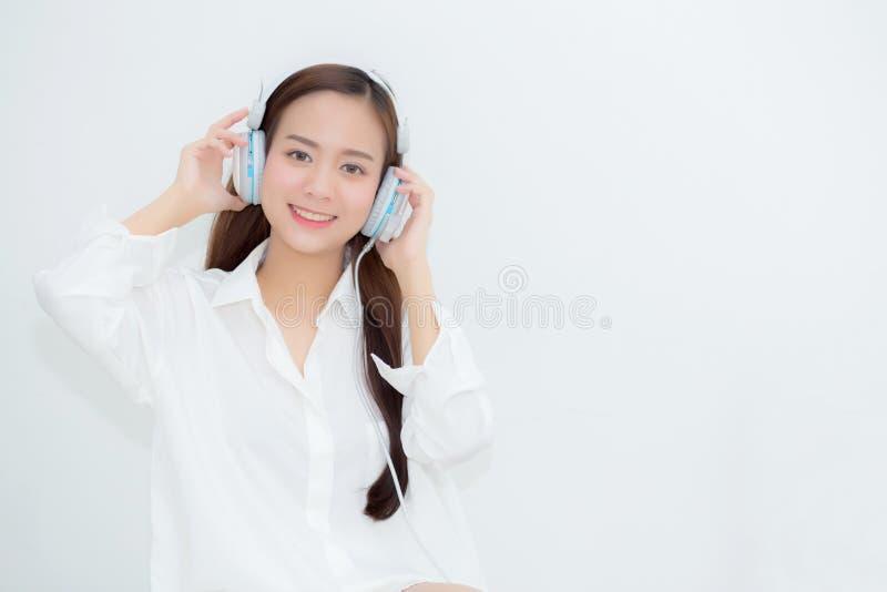 A jovem mulher asiática do retrato bonito feliz aprecia e o divertimento escuta música com o fones de ouvido que senta-se na sala foto de stock royalty free