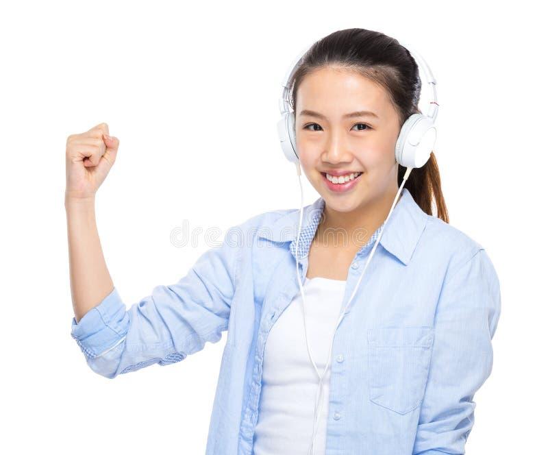 A jovem mulher asiática escuta a música com fones de ouvido e o braço aperta foto de stock