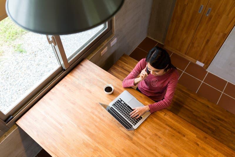 A jovem mulher asiática faz chamar o telefone esperto e o trabalho na nota foto de stock