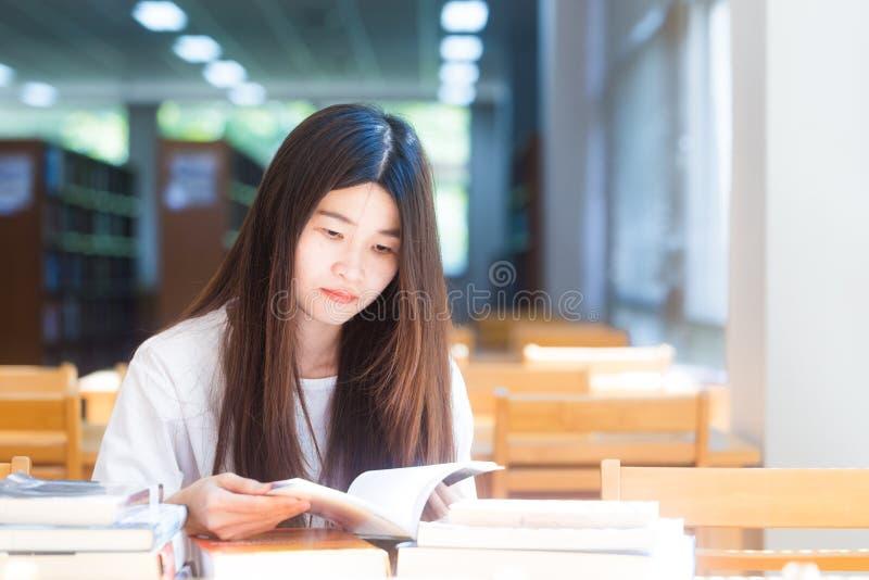 Jovem mulher asiática feliz do estudante que pensa com o livro na biblioteca imagem de stock royalty free