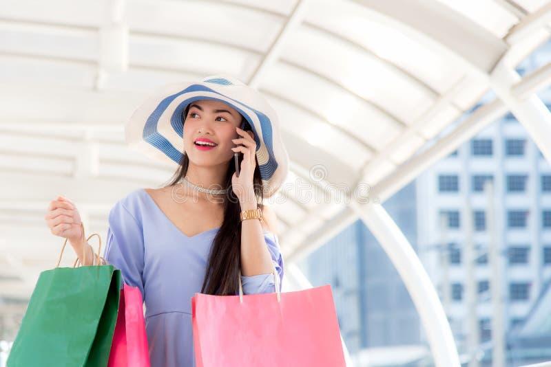 Jovem mulher asiática na cidade com sacos de compras que fala no telefone celular fotografia de stock