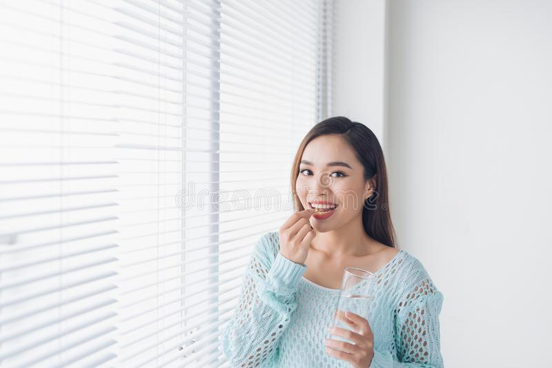Jovem mulher asiática nova da beleza que come comprimidos e água potável foto de stock royalty free