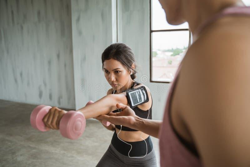 Jovem mulher asiática que faz exercícios do peso com auxílio de seu instrutor pessoal imagens de stock royalty free