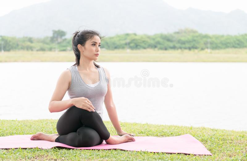 Jovem mulher asiática que faz a prática da ioga no fundo do parque da saúde foto de stock royalty free