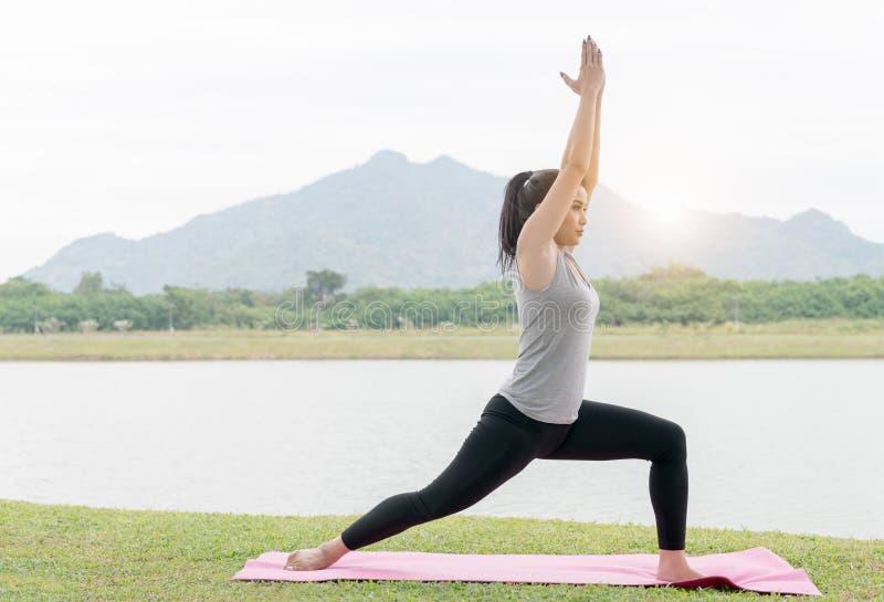 Jovem mulher asiática que faz a prática da ioga no parque da saúde fotos de stock