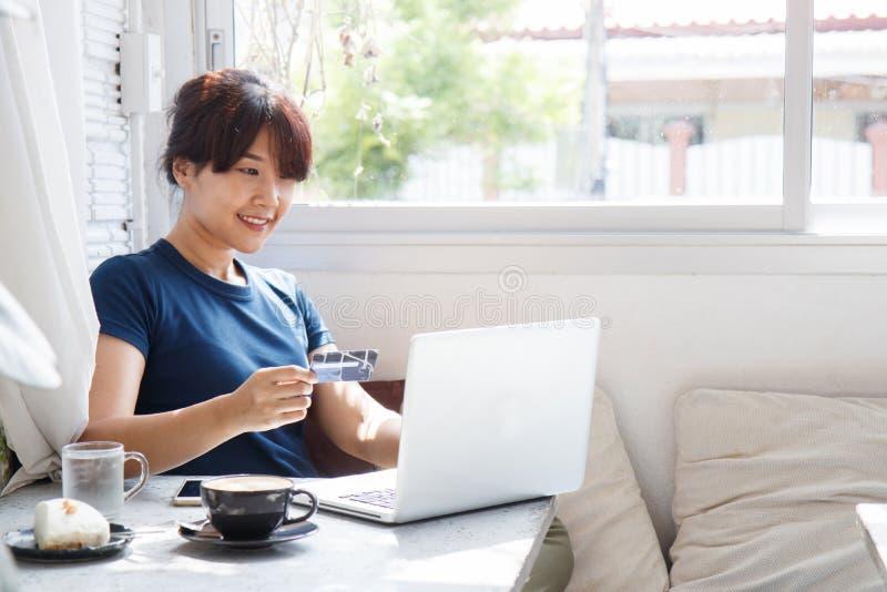 Jovem mulher asiática que guarda o cartão de crédito e que usa o laptop imagem de stock royalty free