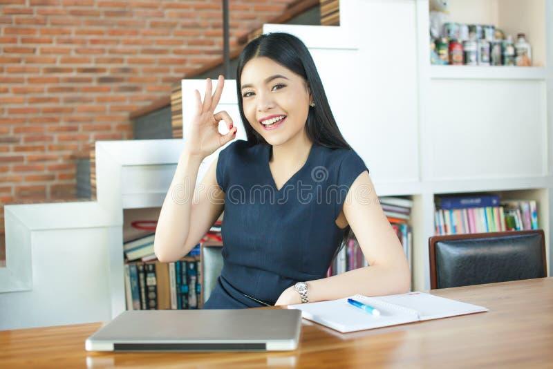Jovem mulher asiática que senta-se com laptop e sinal aprovado fotos de stock royalty free