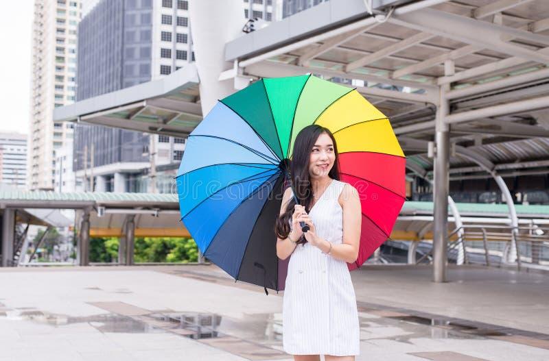 Jovem mulher asiática que smling e que guarda o guarda-chuva na cidade, no conceito do estilo de vida, em feliz e sorriso imagem de stock