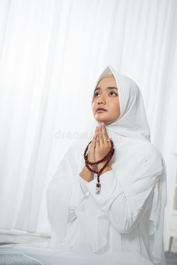 Jovem mulher asiática rezando com o al-Qur 'e os grânulos de oração fotos de stock