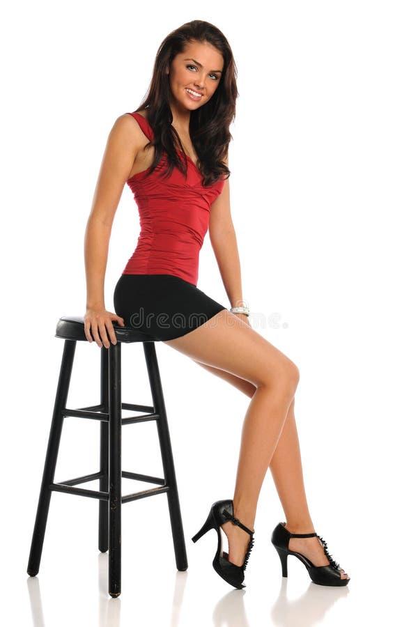 Jovem mulher assentada no tamborete imagem de stock royalty free