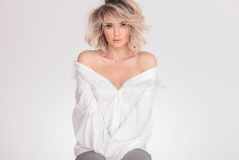 Jovem mulher assentada que veste uma camisa bouffant com ombros despidos imagem de stock royalty free
