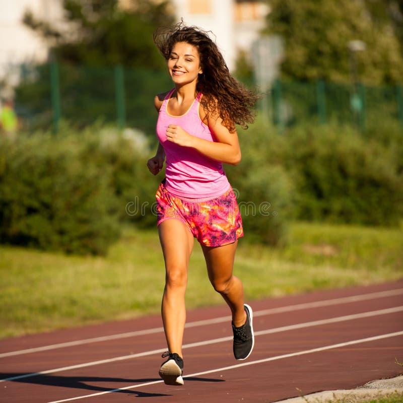 A jovem mulher ativa corre na trilha atheltic na tarde do verão imagem de stock royalty free