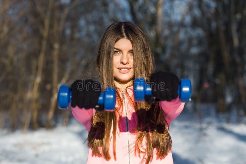 A jovem mulher ativa executa um exercício com pesos imagens de stock royalty free
