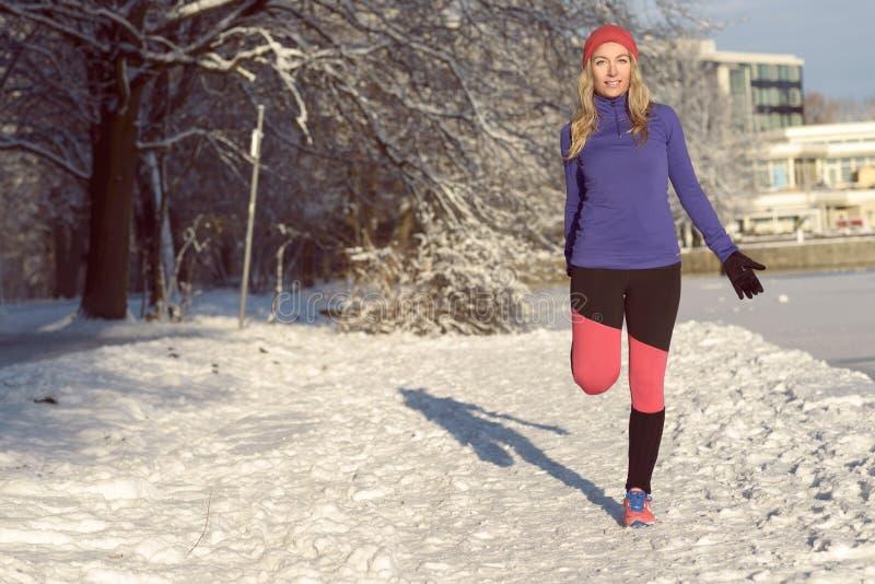 Jovem mulher ativa que exercita na neve fotos de stock royalty free