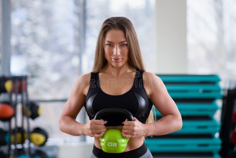 Jovem mulher atlética durante o exercício na classe da aptidão Menina bonita com corpo perfeito e a forma que guardam o kettlebel imagens de stock