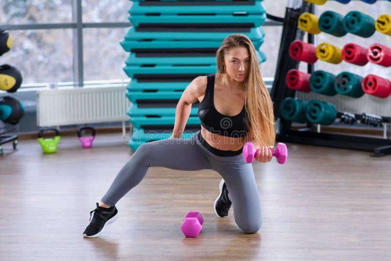 Jovem mulher atlética durante o exercício na classe da aptidão Menina bonita com corpo perfeito e a forma que levantam com imagem de stock royalty free