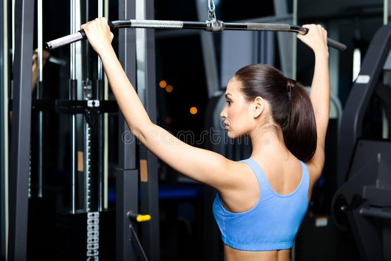 A jovem mulher atlética elabora no simulador imagem de stock royalty free