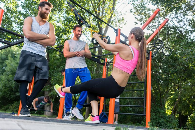A jovem mulher atlética que faz o bíceps ondula com um instrutor da suspensão fotografia de stock
