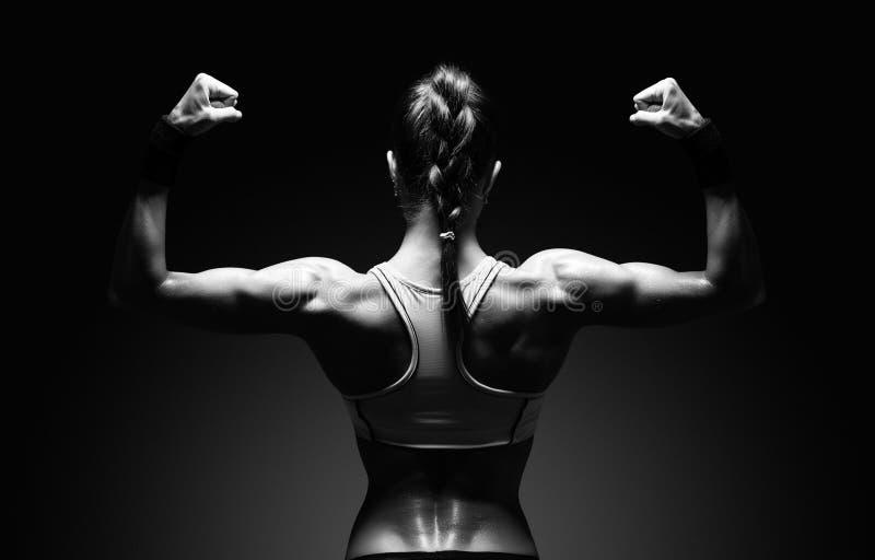 Jovem mulher atlética que mostra os músculos da parte traseira foto de stock