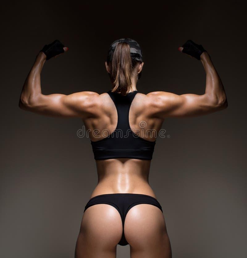 Jovem mulher atlética que mostra os músculos da parte traseira fotos de stock royalty free