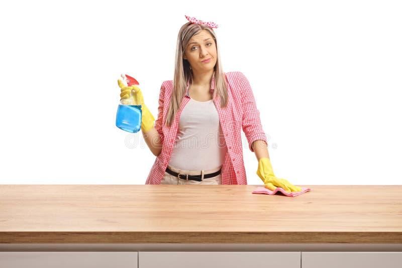 Jovem mulher atrás de um contador de madeira alimentado acima de imagens de stock royalty free