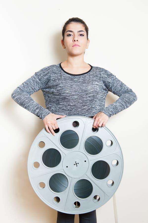Jovem mulher atrás do carretel grande do filme do cinema foto de stock