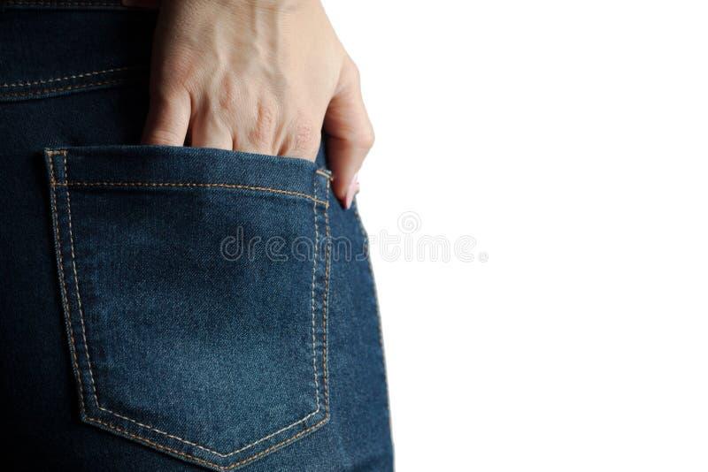 jovem mulher atrás em calças de brim da sarja de Nimes guarda sua mão no bolso da parte traseira Luz dura Fundo isolado branco foto de stock royalty free