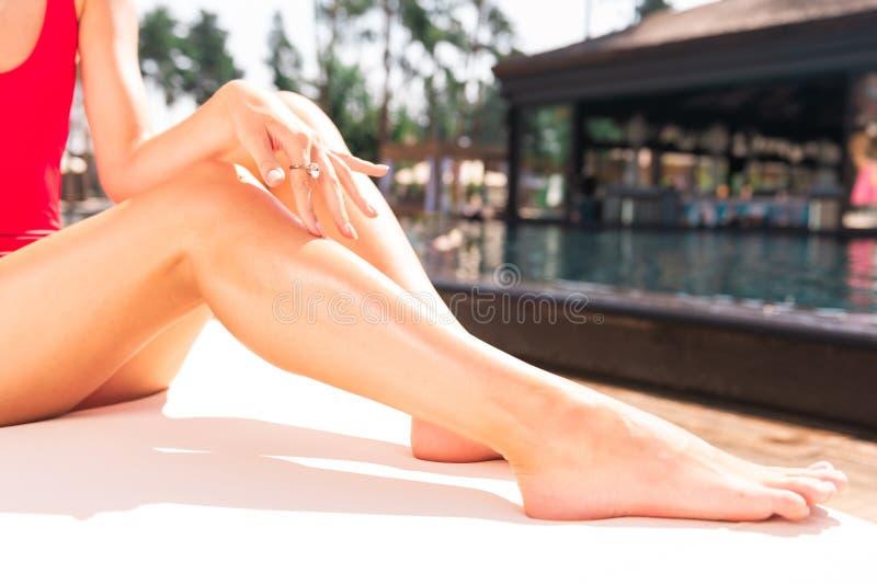 Jovem mulher atrativa agradável que toca em seus pés imagem de stock royalty free