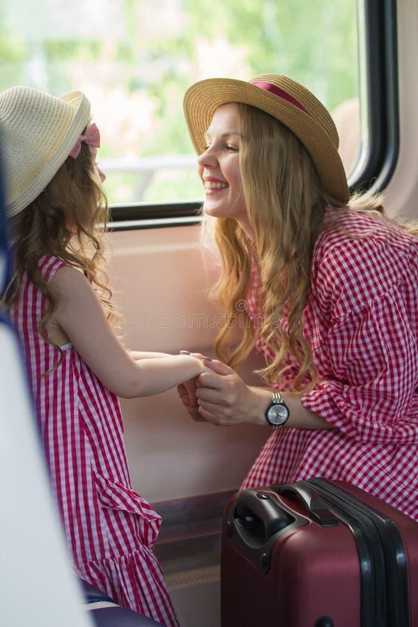 A jovem mulher atrativa beija sua filha bonito na frente da janela no trem fotografia de stock royalty free