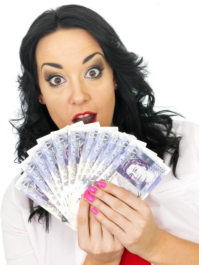 Jovem mulher atrativa chocada feliz que guarda o dinheiro fotografia de stock royalty free