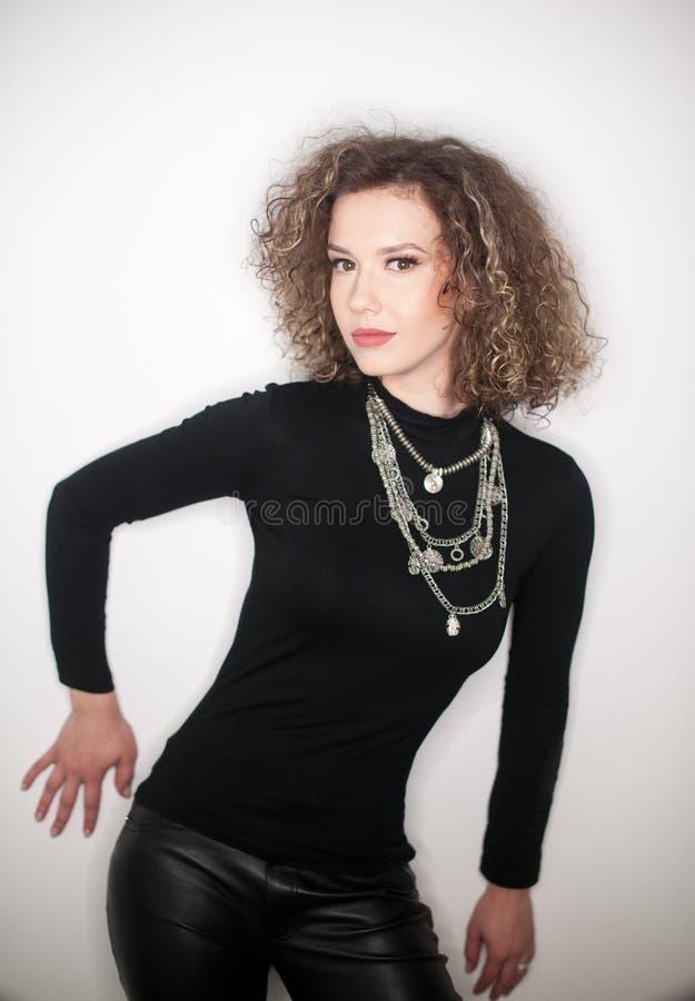 Jovem mulher atrativa com a blusa preta da gola alta contra a parede branca Menina bonito com cabelo encaracolado longo no equipa foto de stock