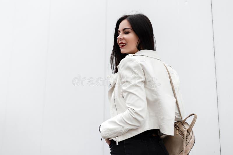 A jovem mulher atrativa com bordos vermelhos com um sorriso bonito em um casaco de cabedal branco elegante com uma trouxa à moda  fotos de stock