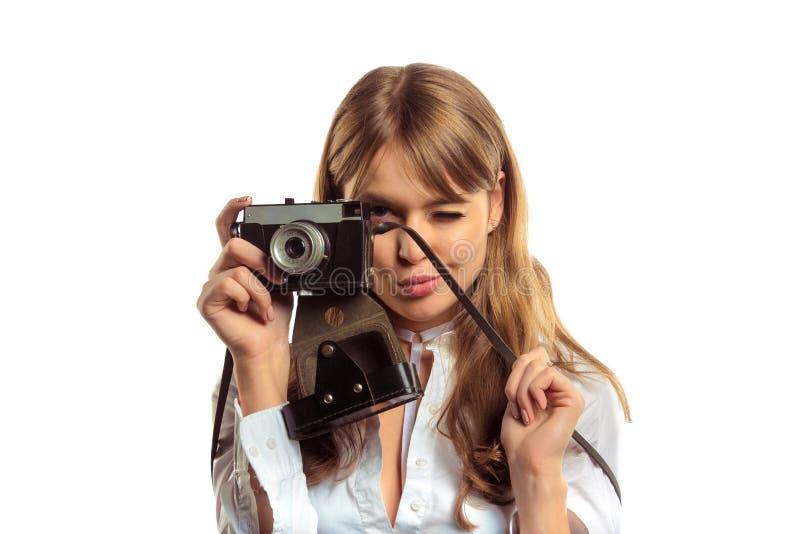 Jovem mulher atrativa com a câmera da foto do vintage que faz o tiro fotografia de stock