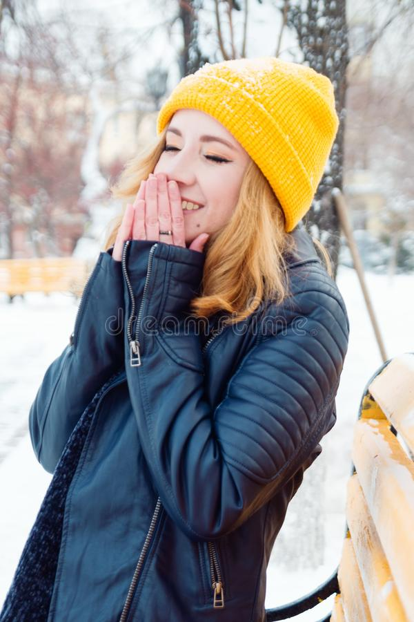 A jovem mulher atrativa com cabelo louro em um chapéu de confecção de malhas amarelo está aquecendo suas mãos no parque do invern fotografia de stock royalty free