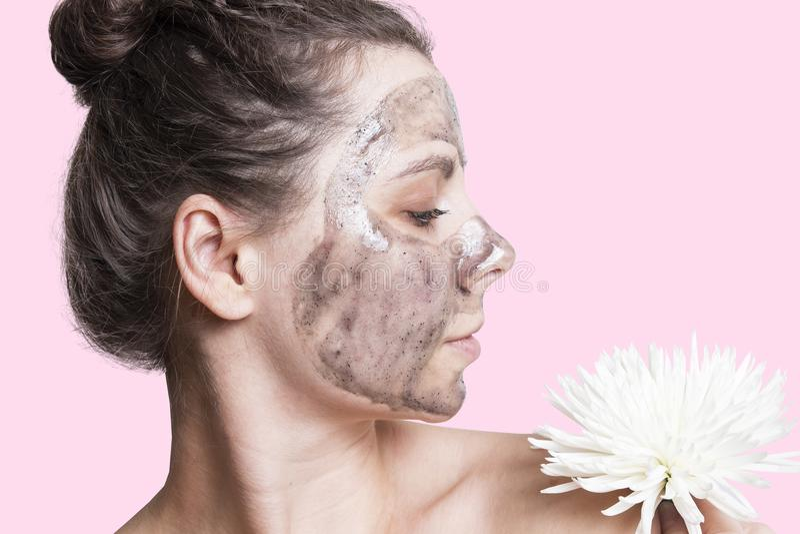 Jovem mulher atrativa com máscara de creme na cara Conceito dos cuidados com a pele da cara Pele lisa saudável na cara do ` s da  foto de stock