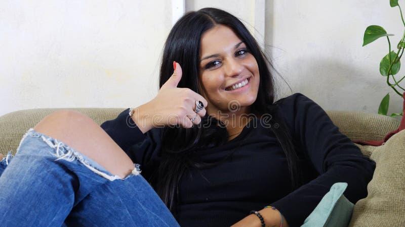 Jovem mulher atrativa com o polegar que faz acima o sinal APROVADO foto de stock royalty free
