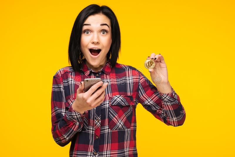 Jovem mulher atrativa com o smartphone, guardando o bitcoin, moeda do metal da cor dourada, moeda futura isolada no fundo amarelo foto de stock