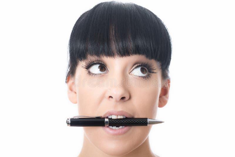 Jovem mulher atrativa confusa furada pensativa com a pena na boca foto de stock