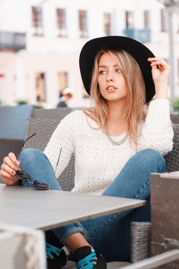 A jovem mulher atrativa de encantamento em uma camiseta branca do vintage em calças de brim à moda nas sapatilhas em um chapéu el imagem de stock
