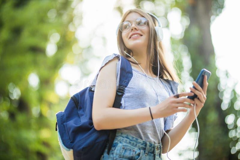 Jovem mulher atrativa de sorriso com trouxa que escuta a música do telefone no parque imagem de stock