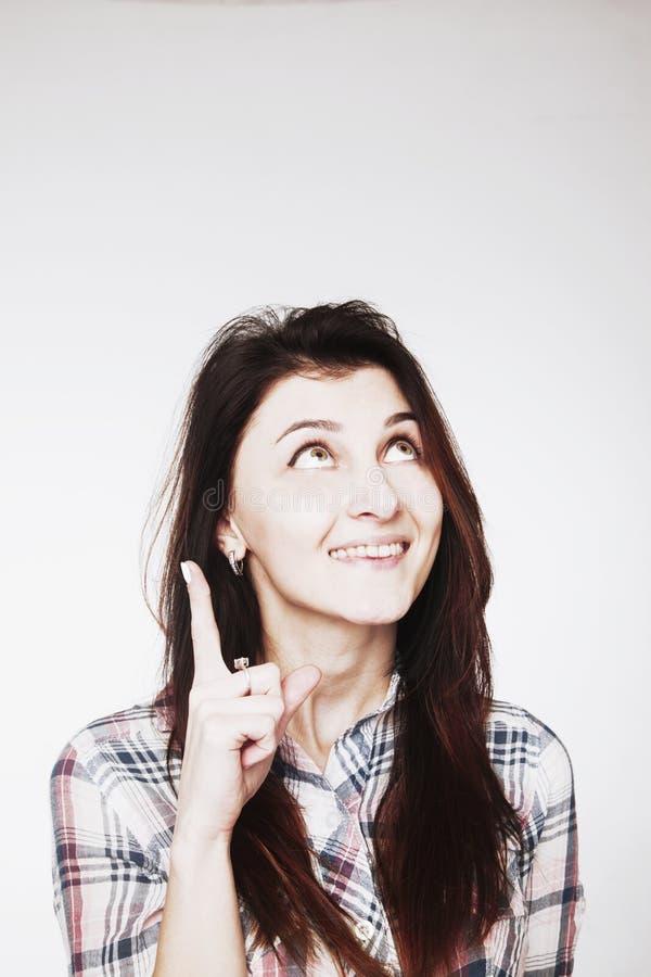 Jovem mulher atrativa de sorriso que aponta para cima com seu dedo imagens de stock royalty free